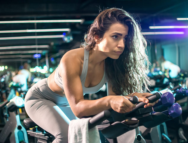 Woman on bike doing indoor cycling in spin class - Chafing From Spin Class -